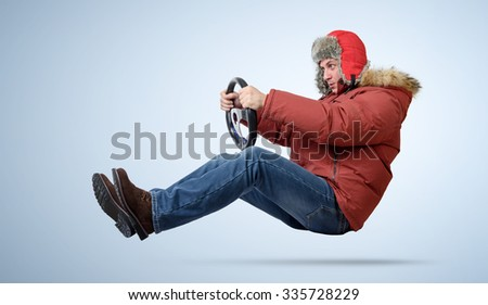 Funny man in cap driving a car in winter - stock photo