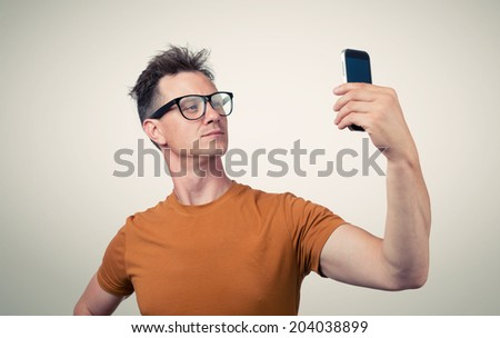 Funny man in glasses photographs himself - stock photo