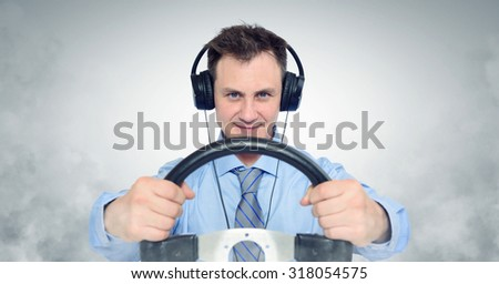 Funny man in headphones with a steering wheel, car drive concept - stock photo
