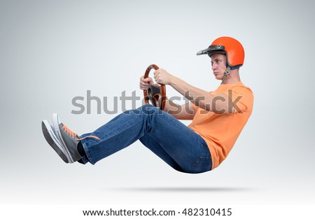 Funny man in helmet car driver with wooden steering wheel, auto concept