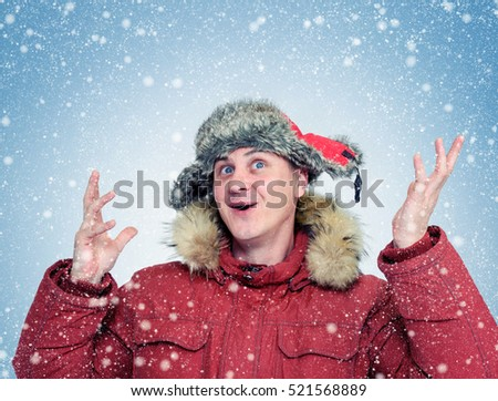 Funny Man in winter clothes enjoys the snow.