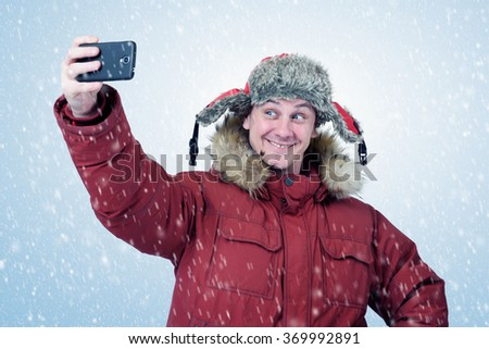 Funny man in winter clothes make selfie on smart phone, is snowfall - stock photo