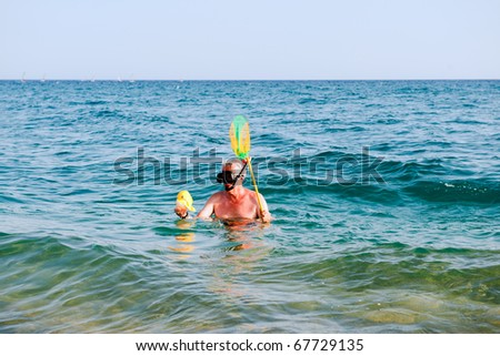 Funny man is snorkeling with fishing net and plastic fish - stock photo