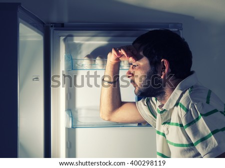 funny man looking into refrigerator