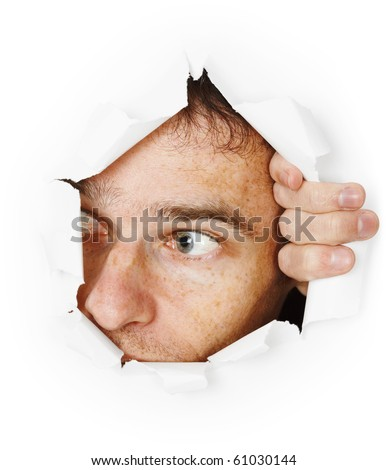 Funny man looking through hole in paper - face close up - stock photo