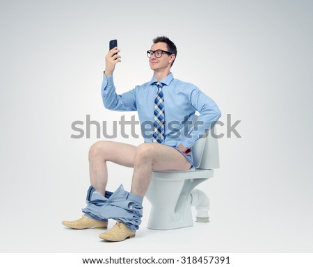 Funny man photographing himself in the toilet - stock photo