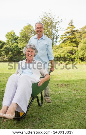 Funny man pushing his wife in a wheelbarrow outside in the sunshine