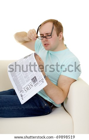 Funny man reading a job advertisement in the newspaper on white - stock photo