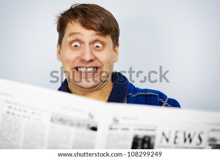 Funny man reading a newspaper. Shocked bad news. - stock photo