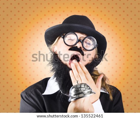 Funny man wearing plastic moustache, phony beard and geek glasses falling asleep with silver service bell in hand, depicting slow service - stock photo