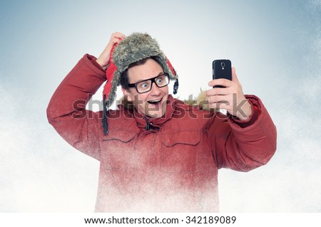 Funny man with glasses and winter clothes make selfie smart phone - stock photo