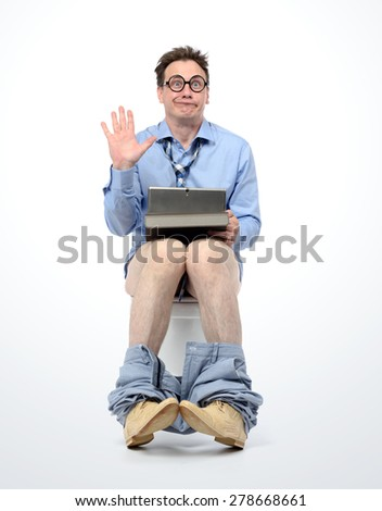 Funny man with tablet pc sitting on the toilet - stock photo