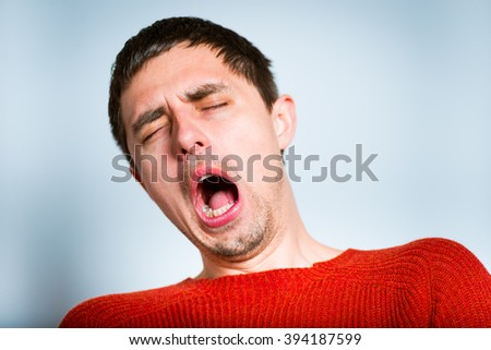 funny man yawns, isolated on a gray background - stock photo