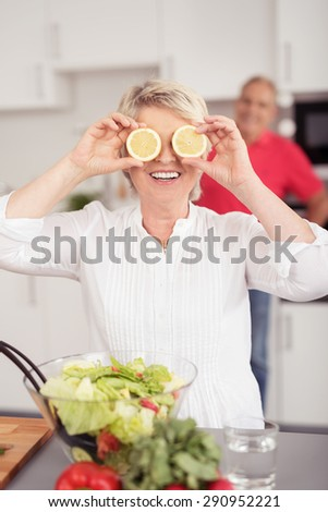 Funny Middle Aged Wife Holding Two Lemon Slices In Front of Eyes While Preparing Fresh Vegetable Salad at the Kitchen. - stock photo