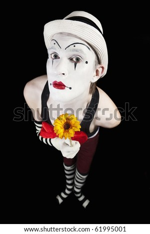 Funny mime in white hat with a bouquet of flowers on a black background - stock photo