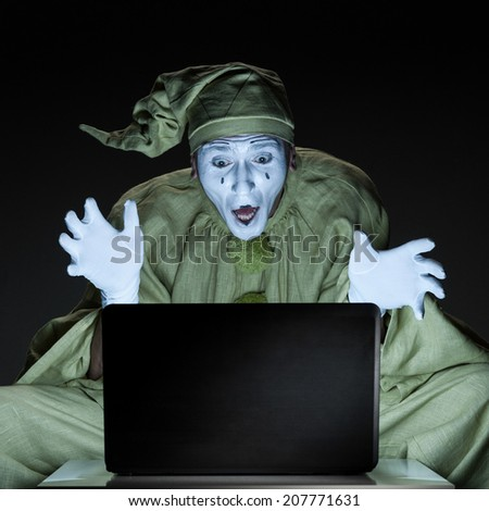 funny mime sitting near laptop and show happy expression - stock photo