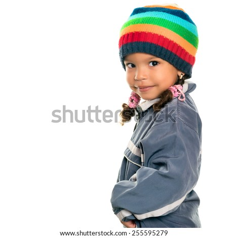 Funny mixed race small girl wearing winter clothes and a colorful beanie hat isolated on white - stock photo