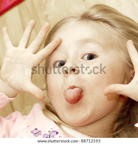 Funny mocking little blond girl. See my portfolio for more - stock photo