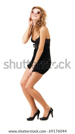 Funny model in sunglasses and in a little black dress, white background - stock photo