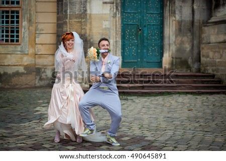 Funny modish wedding couple dances on the carriage road
