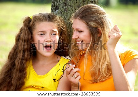 Funny mom and daughter listening music in headphones outdoors - stock photo