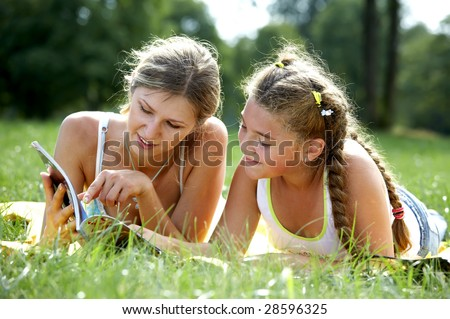Funny mom and daughter reading outdoors - stock photo