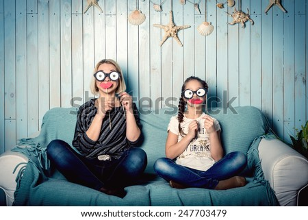 funny mom and daughter with false mustaches, playing at home - stock photo