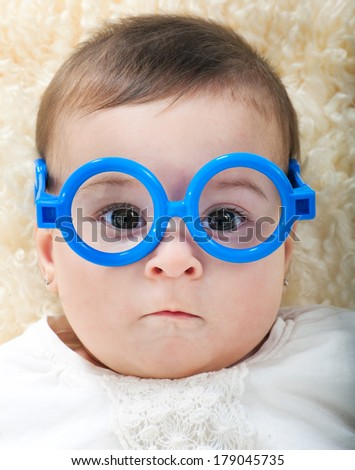 Funny 6 month old baby girl in glasses - stock photo