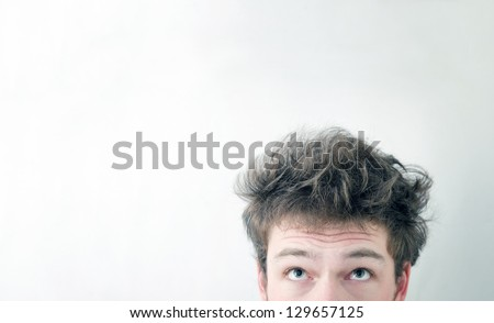 "Funny morning look of a young adult men with on a white (greenish/blueish) background - not ""isolated"". This is also the Hangover or just ""a bad night"" look. You can see a bit of fatigue. - stock photo"