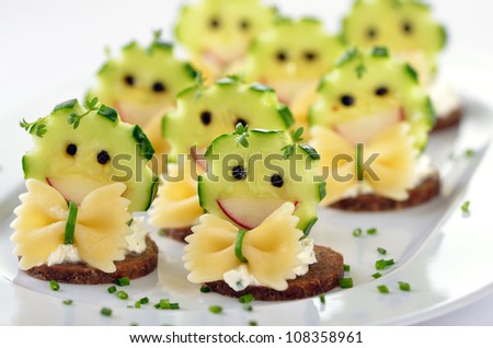 Funny morsels with spicy cream cheese, decorated with cucumber, radishes, pasta and pepper - stock photo