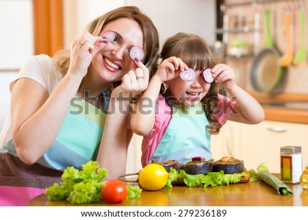 Funny mother and daughter playing with vegetables in kitchen, family and healthy food - stock photo