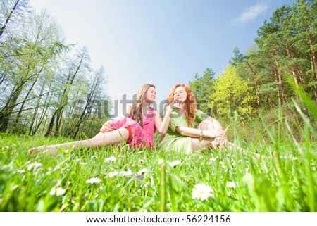 funny mother and daughter sitting on green grass
