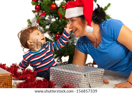 Funny mother with Santa hat and her baby son in front of Christmas tree - stock photo