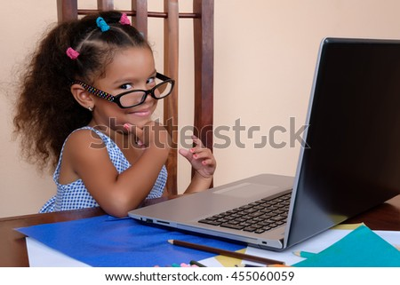 Funny multiracial small girl wearing glasses and using a laptop computer at home - stock photo
