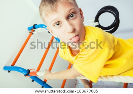 Funny naughty child playing on sports equipment showing his tongue - stock photo