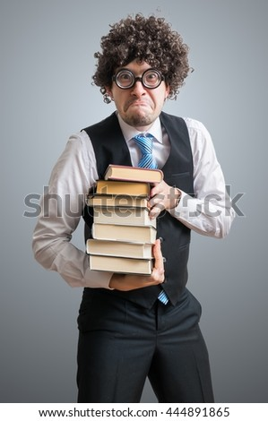 Funny nerd student is hiolding books. - stock photo
