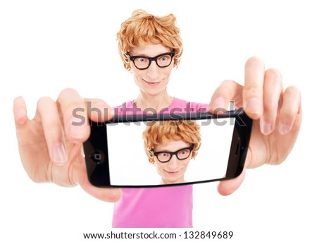 Funny nerdy guy is taking a self portrait with a smart phone - stock photo