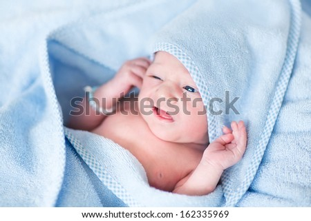 Funny newborn baby covered n a blue bath towel - stock photo