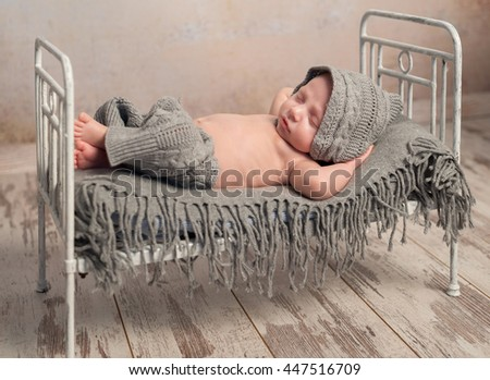 funny newborn baby in knitted hat and pants sleeping on old retro cot with plaid with hands behind head - stock photo
