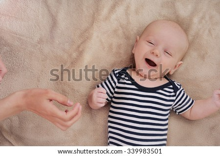 funny newborn boy singing song under care mother; singing cute newborn baby; maternity concept; soft image of beautiful family - stock photo