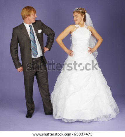 Funny Newlyweds standing on a blue background - stock photo