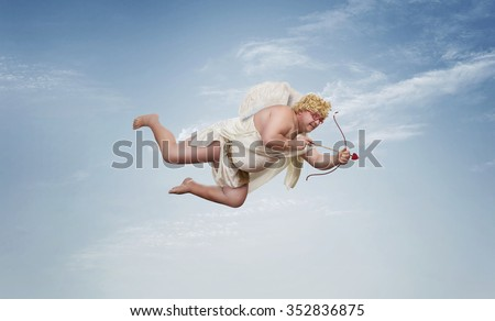 Funny overweight cupid aiming with the arrow of love over clear blue sky with copy space - stock photo