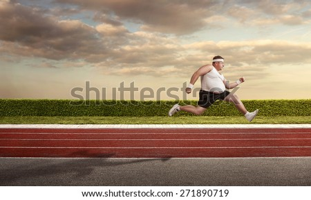 Funny overweight man speeding on the running track with copy space - stock photo