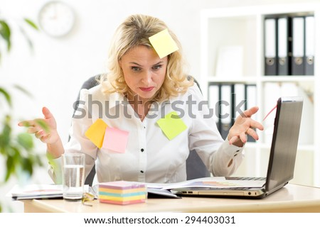 Funny overworked businesswoman working in office and looking at stickers reminder notes - stock photo