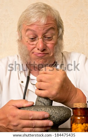 Funny pharmacist preparing medication with mortar and pestle - stock photo