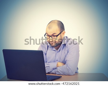 Funny photo of businessman bald with beard wearing shirt and glasses.  angry businessman working with laptop at table. Isolated on  background