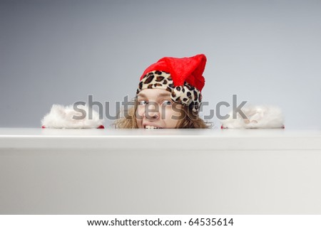 Funny photo of the afraid Santa Claus hidden under the table. Gray background can be easily replaced by any others - stock photo