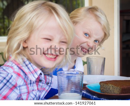 Funny photo of two children eating with bad manners. One child is poking out his tongue. - stock photo
