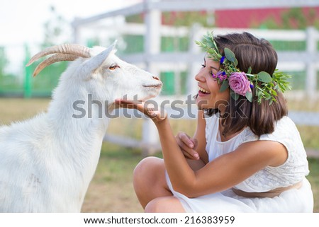 Funny picture a beautiful young girl farmer with a wreath on her head with white goat. - stock photo