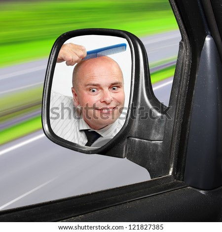 Funny picture of a careless driver combing his hairless head.  Highway traffic safety concept. - stock photo
